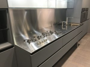 Aran-kitchen-with-stainless-steel-countertop-and-backsplash