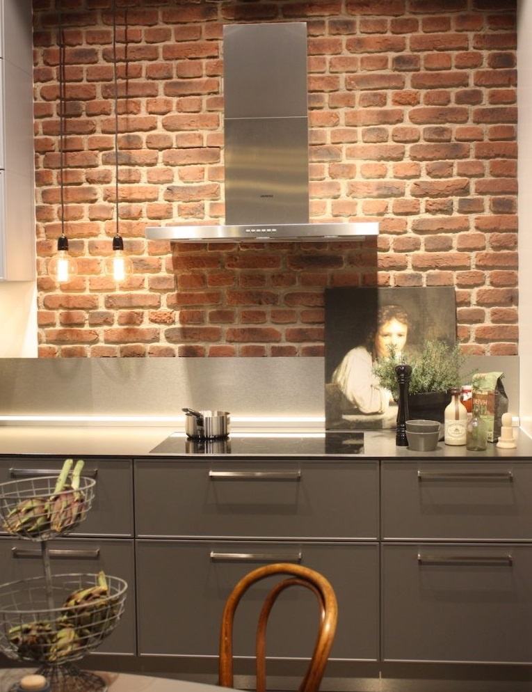 Exposed-brick-with-stainless-steel-countertop-and-a-small-backsplash